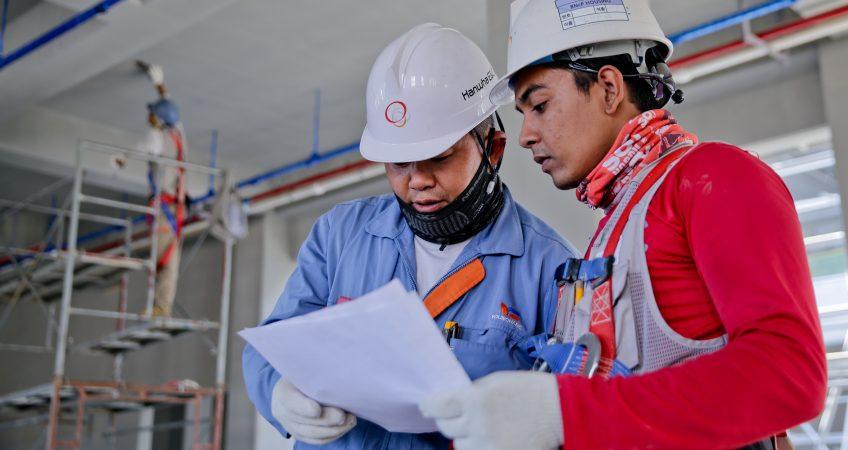 Dos trabajadores de la construcción consultando un plan de seguridad y salud